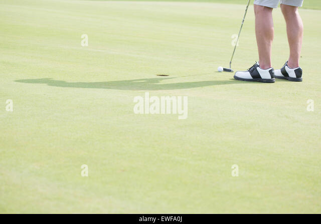Low section of middle-aged man playing golf - Stock Image