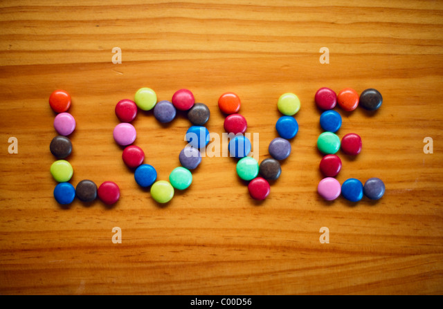Love on wooden bench in sweeties - Stock Image