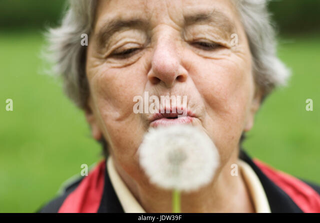 Older woman blowing dandelion in park - Stock Image