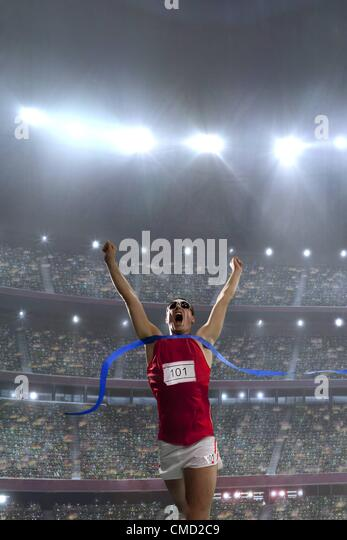 08.11.2011. Model released picture of a male athlete celebrating his victory in an athletics stadium in front of - Stock Image
