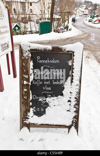 The Netherlands, Slenaken, Sign of outdoor cafe, covered with snow. - Stock Image