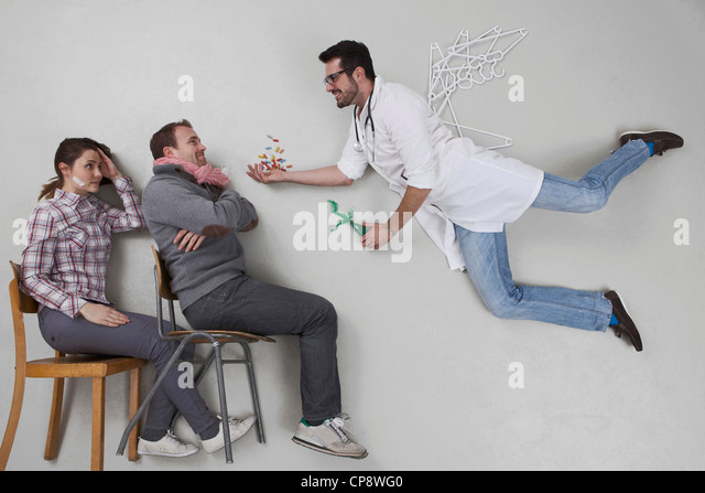 Doctor giving medicine to sick patient - Stock Image