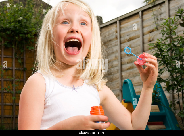 young girl having fun blowing bubbles - Stock Image
