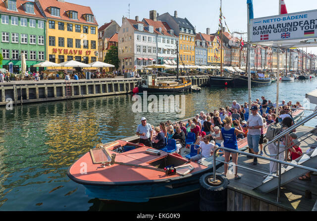 A canal and harbour tour cruise boat prepares to leave its base in Nyhavn, Copenhagen, Denmark. - Stock Image