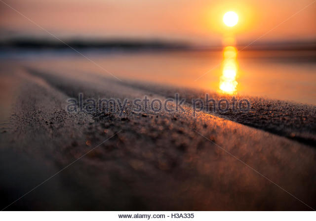 sunset on the beach shot at a low angle - Stock Image