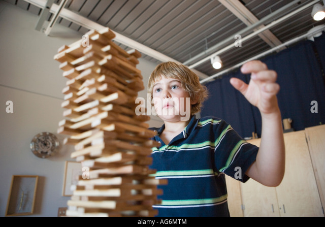 eight year old boy stacking wood blocks as high as he can, watching to make sure they don't topple over - Stock-Bilder