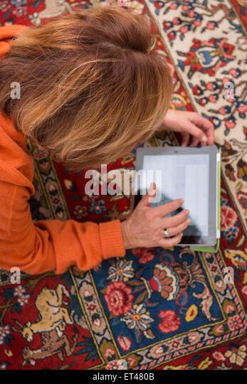 Relaxed senior woman working a digital tablet, Munich, Bavaria, Germany - Stock-Bilder