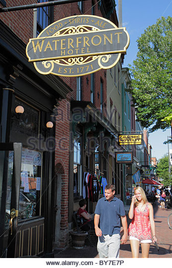 Baltimore Maryland Fells Point historic district neighborhood business Waterfront Hotel man woman couple stroll - Stock Image