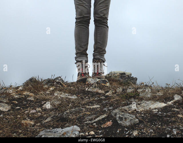 Legs and Feet of Person Standing on Rocky Ground - Stock Image