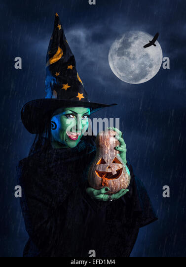 Witch with green skin holding carved Halloween pumpkin at moon and dark sky with rain - Stock Image
