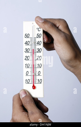 Weather temperature meter showing 35 degrees celsius centigrade close up of Temperature meter holding in both hands - Stock Image