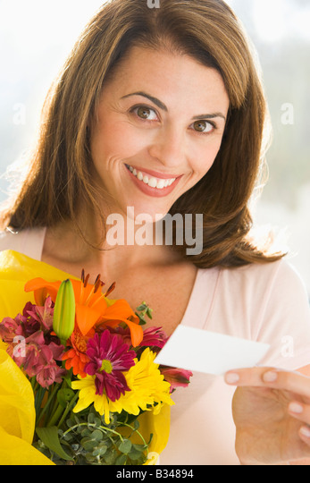 Woman holding flowers and note smiling - Stock Image