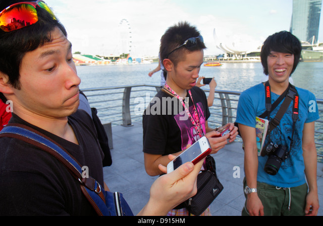 Singapore Singapore River Marina Bay Merlion Park Asian man looking at smart phone reacting reacts to picture - Stock Image