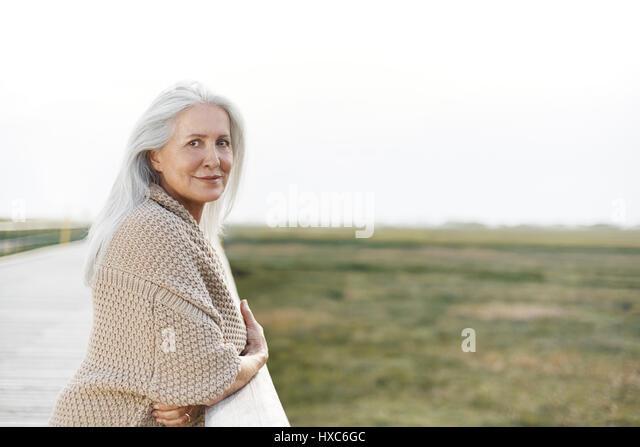 Portrait confident senior woman leaning on boardwalk railing - Stock Image