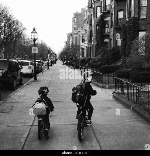 Two Boys Riding Bicycles on Urban Sidewalk, Rear View - Stock-Bilder