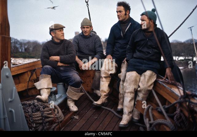 fishermen on a boat in caps hats and waders - Stock-Bilder