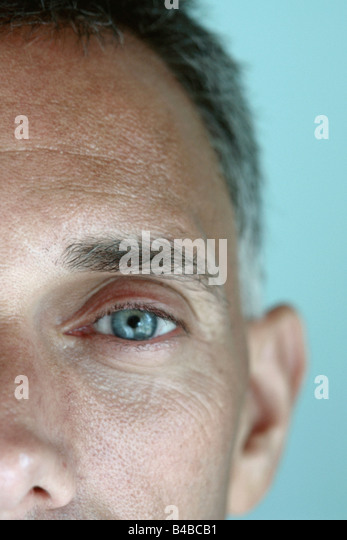 Closeup Portrait of a Baby Boomer Man with Piercing Blue Eyes Using Selective Focus He is Looking into Camera Lens - Stock Image