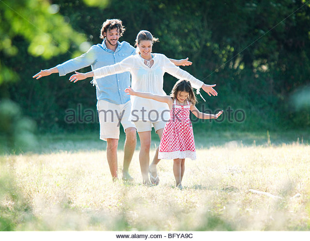 Family fun walking in country field - Stock Image