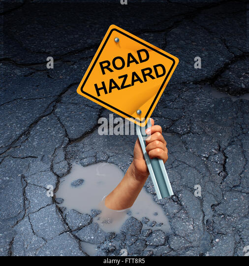 Road hazard concept as an accident victim drowning in a broken street pothole while holding a traffic sign as a - Stock-Bilder