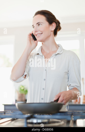 Woman on cell phone cooking - Stock Image