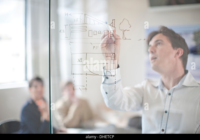 Man drawing architectural plans on glass wall, colleagues in background - Stock-Bilder