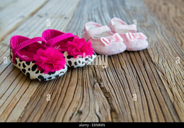 Sweet fancy and colorful baby shoes on the wooden table - Stock Image