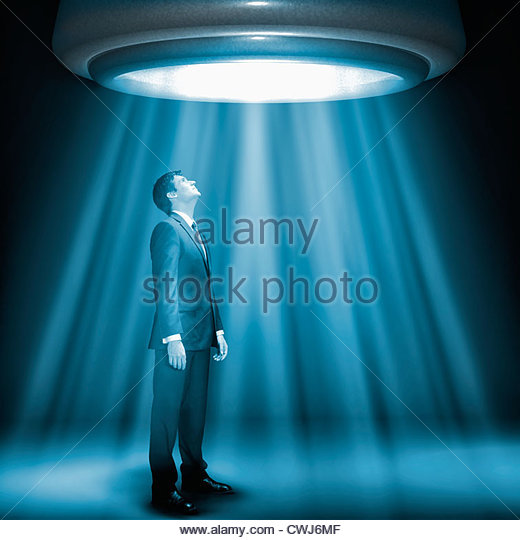 Caucasian businessman standing underneath glowing lights - Stock Image