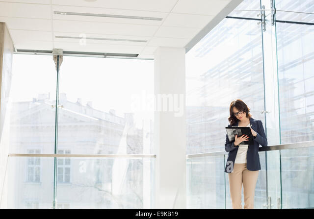 Businesswoman reviewing documents in office - Stock Image