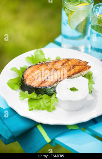 Grilled salmon steak on a fresh green salad with garlic sauce - Stock Image