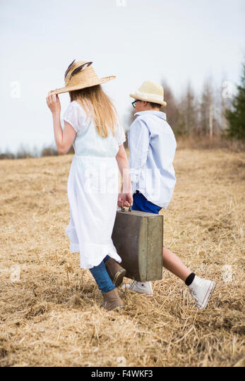 Finland, Keski-Suomi, Aanekoski, Girl (12-13) and boy (12-13) walking in field and carrying suitcase - Stock Image
