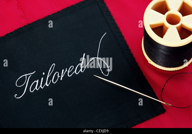 Photo of a garment label with the word Tailored on a red silk lining with a needle and reel of thread. - Stock Image