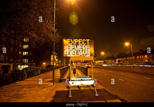 Road sign in urban scene at night, London, England - Stock-Bilder