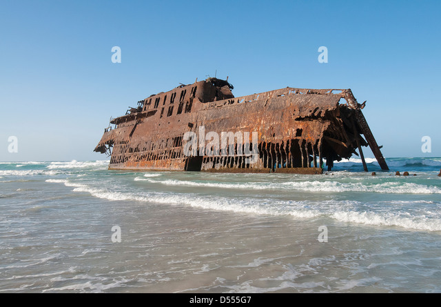 Shipwreck stranded on beach - Stock Image