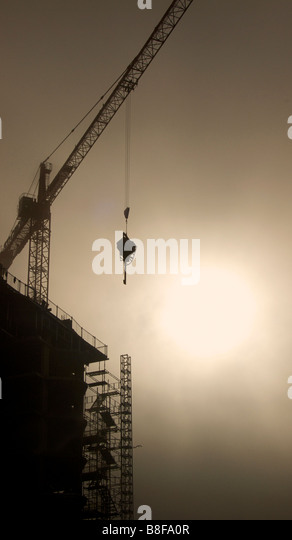 Unnidentifiable Construction site Silhouetted against the sun. Crane lifting equipment. - Stock-Bilder