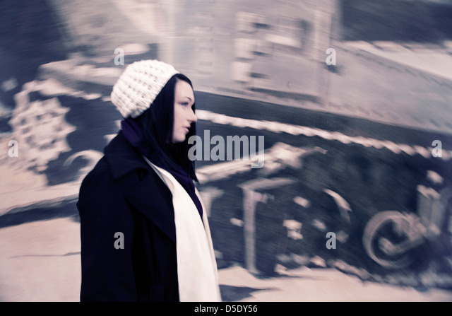 Woman walking quickly by wall - Stock-Bilder