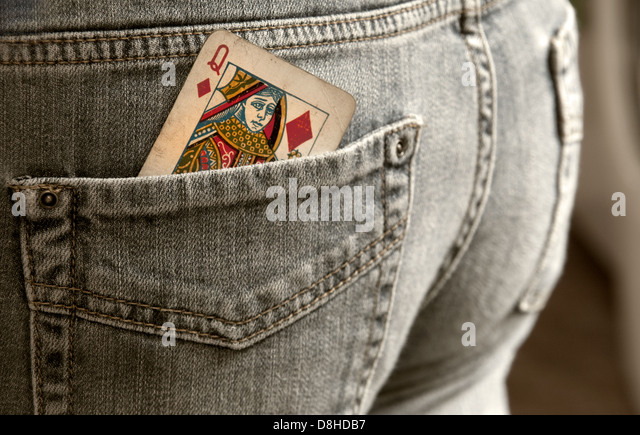 How to gamble Queen of diamonds playing card in a back pocket of a pair of jeans - Stock Image