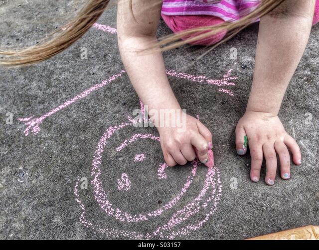 Toddler Caucasian girl draws stick figure with chalk - Stock Image