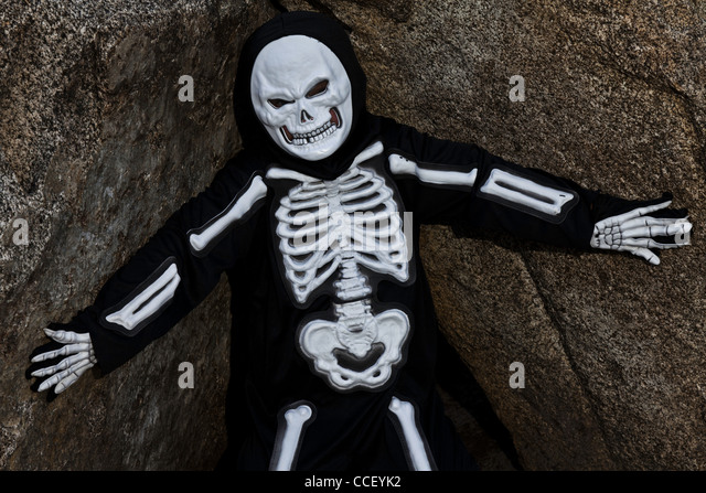 Boy dressed up as skeleton posing on rock - Stock Image