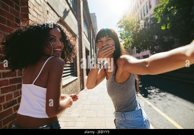 Shot from behind of two young women walking on city street. Female friends walking together outdoors and having - Stock Image