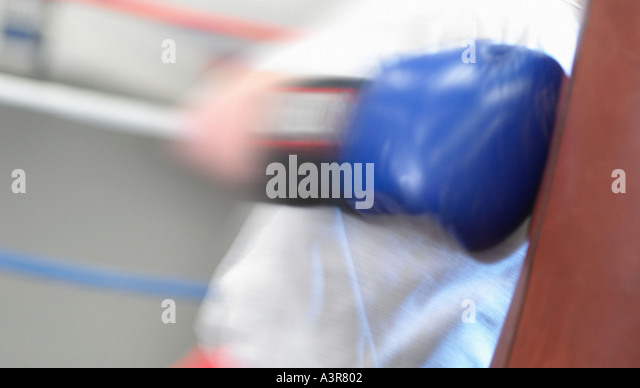 Male wist hitting boxing bag - Stock Image
