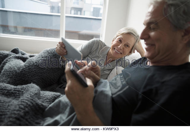 Senior couple relaxing,using digital tablet and smart phone in bed - Stock Image
