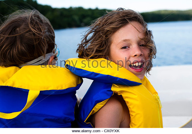 Children on a boat in lifejackets - Stock Image