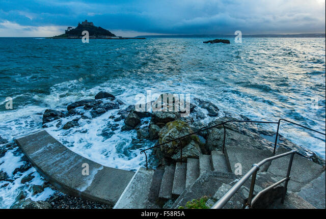 St Michael's Mount as seen from Marazion in Cornwall on a high tide in the early evening. - Stock Image