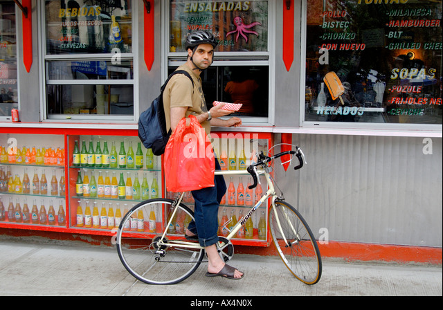A man on a bike stops for a hotdog at a take out place in Lower Manhattan. Stock Photo
