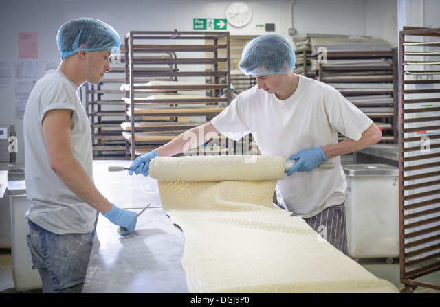 Bakers in protective clothing preparing length of dough - Stock Image