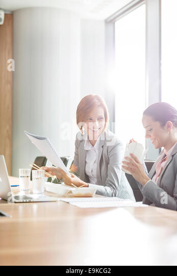 Young businesswomen having lunch at table in office - Stock Image