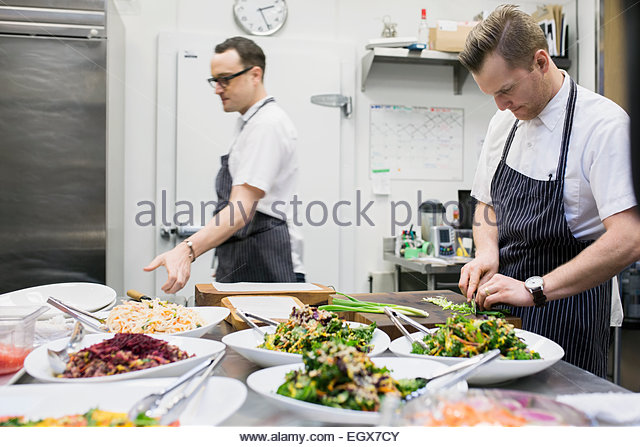 Chefs cooking in commercial kitchen - Stock Image