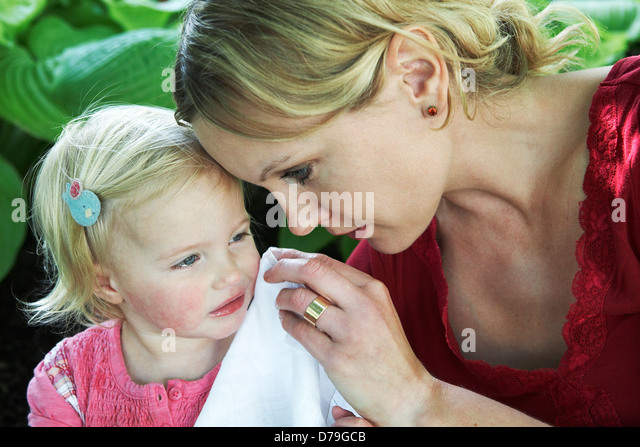 Mother dries the tears of her toddler daughter. - Stock Image
