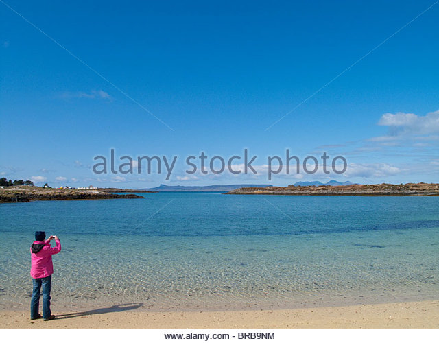 Woman taking photograph of tranquil ocean under blue sky - Stock Image