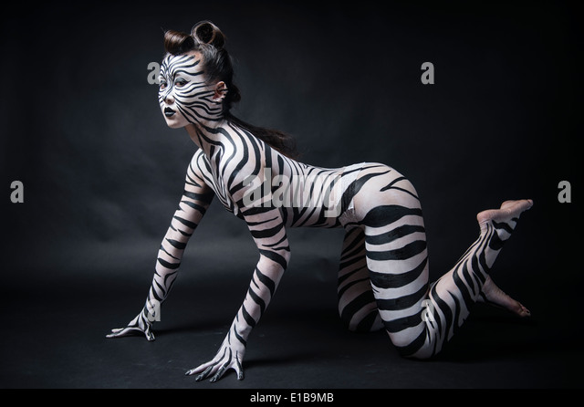 A woman with her body painted in black and white zebra stripes on her hands and knees like an animal - Stock Image
